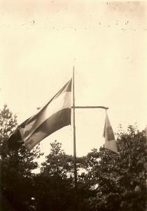 Onze groepsvlag naast de Nederlandse driekleur in de mast tijdens het verkennerskamp Dwingeloo in augustus 1948
