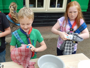 Welpen aan de afwas tijdens het kamp